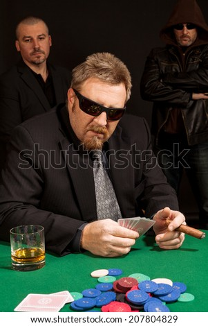 Photo of a man playing poker while wearing sunglasses and smoking a cigar.  - stock photo