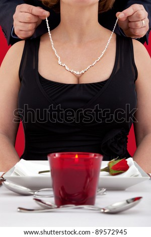 Photo of a man putting a diamond necklace around the neck of his wife , who is sat at a table in a restaurant celebrating her birthday or their wedding anniversary. - stock photo