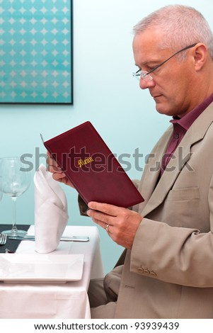 Photo of a man reading the menu in a restaurant - stock photo