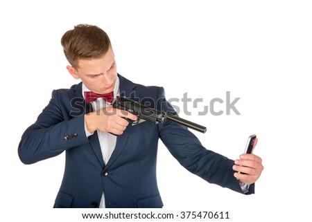 Photo of a man shooting a smartphone with a handgun - stock photo