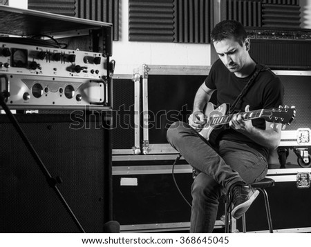 Photo of a man sitting backstage practicing his guitar. - stock photo