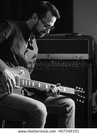 Photo of a man sitting playing his electric guitar in front of a large amplifier. - stock photo