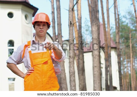 Photo of a manual worker pointing at camera outdoors with a copy space