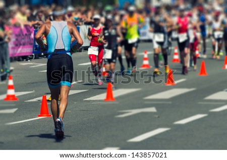 Photo of a marathon competition during an ironman. Use of tilt shift lens for selective focus on the man in the foreground - stock photo