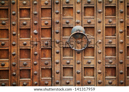 photo of a massive wooden gate with a metal handle