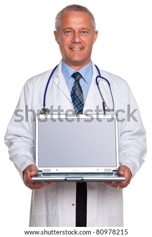Photo of a mature adult male doctor, smiling to camera and holding a laptop computer with clipping path for the blank screen to add your own image of message, isolated on a white background. - stock photo