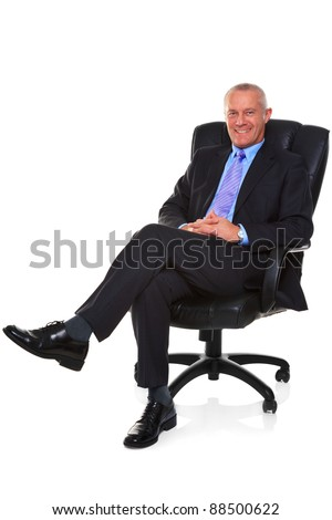 Photo of a mature businessman wearing a smart suit and tie, sat in a leather executive chair with his legs crossed and smiling to camera, isolated on a white background with natural chair reflection. - stock photo