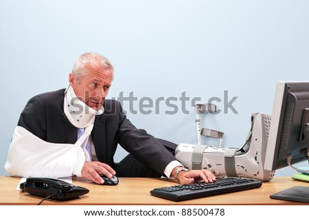 Photo of a mature businessman with multiple injuries sitting at his desk struggling to work on his computer. Good image for health and safety, accident at work or healthcare insurance related themes. - stock photo
