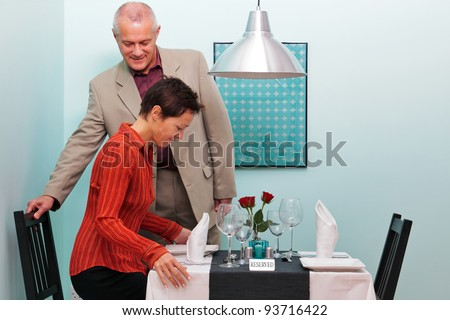 Photo of a mature couple arriving and sitting down at their reserved table in a restaurant - stock photo