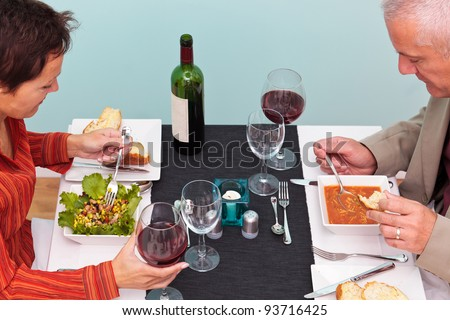 Photo of a mature couple eating starters in a restaurant, she has a bean salad and he has soup. Shot from above. - stock photo
