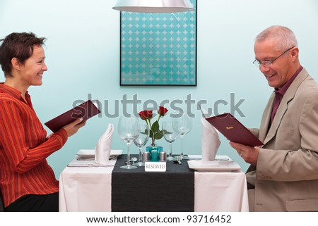 Photo of a mature couple sitting in a restaurant reading the menu - stock photo