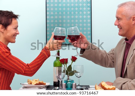 Photo of a mature couple toasting their glasses of red wine whilst sat in a restaurant - stock photo