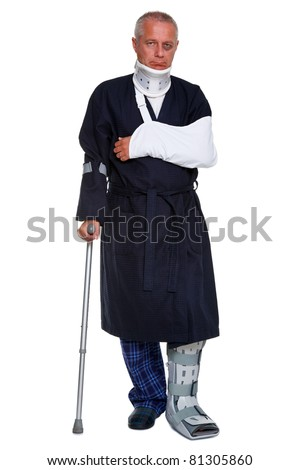Photo of a mature male with various injuries on a crutch, he's wearing a neck brace, arm sling and leg cast and has a black eye, isolated on a white background. - stock photo