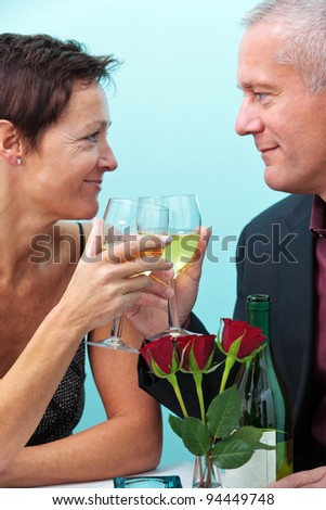 Photo of a mature married couple holding glasses of wine and looking at each other whilst sat in a restaurant. - stock photo