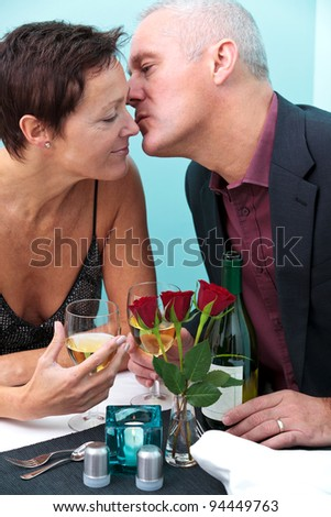 Photo of a mature married couple in a restaurant, he is giving her a kiss on the cheek. - stock photo