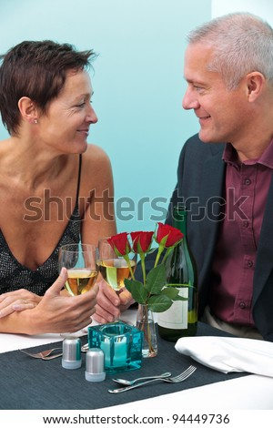 Photo of a mature married couple looking into each others eyes whilst sat at a table in a restaurant - stock photo