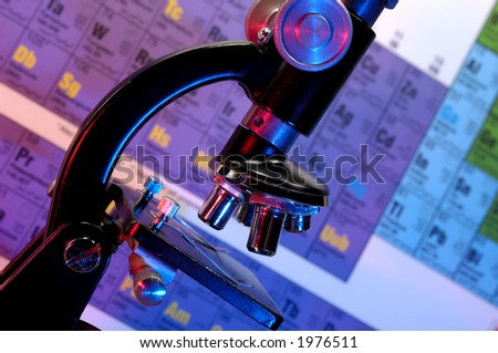Photo of a Microscope and a Periodic Table in The Background - Science Concept - stock photo