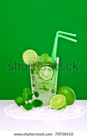 Photo of a Mojito cocktail with fresh lime and mint leaves on a white bar with green background. Made with white rum, sugar, lime juice and soda water with mint leaves poured over crushed ice. - stock photo