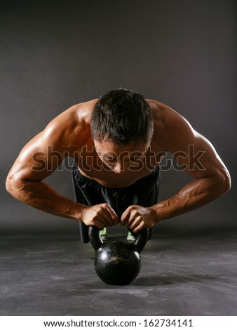 Photo of a muscular Asian man doing pushups with a kettlebell.  - stock photo
