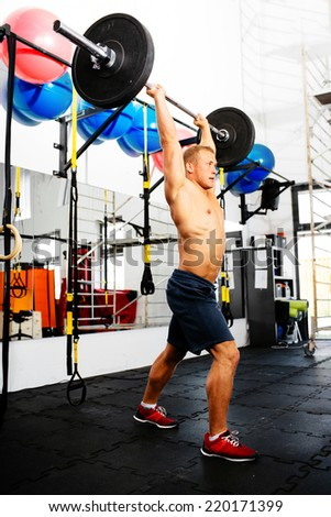 Photo of a muscular athlete pushing the barbell - stock photo