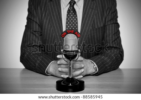 Photo of a news broadcaster sat at a desk and retro microphone with an On The Air illuminated sign, converted to B&W retaining the colour of the text and added vignette for a vintage look. - stock photo
