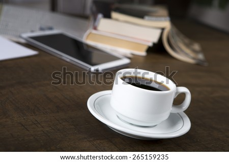 Photo of a no name coffee cup and a stack of books in background on a wood table with shallow depth of field - stock photo