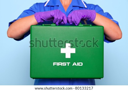 Photo of a nurse in uniform holding a green first aid kit. - stock photo