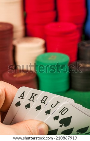 Photo of a person holding a royal flush in front of stacks of gambling chips.