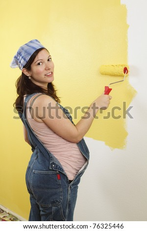 Photo of a pregnant female painting the wall of a bedroom for her future baby. - stock photo