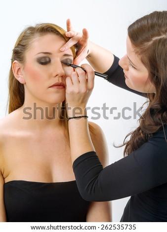 Photo of a professional makeup artist applying eye makeup onto a blond model.  - stock photo