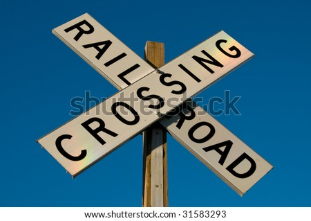 Photo of a railroad crossing sign out in the country. The sun was setting and projected a rainbow light pattern onto the sign. - stock photo