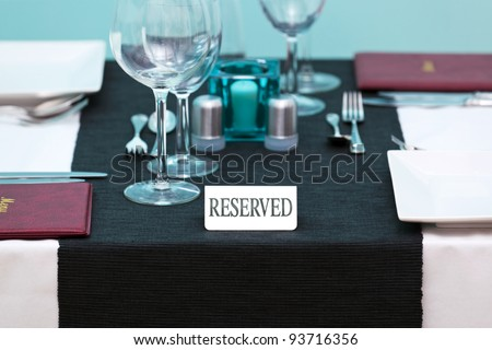 Photo of a Reserved sign on a restaurant table with menus on the side and place settings for two people.