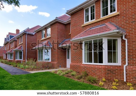 Photo of a row of brand new empty houses for sale on a housing development. - stock photo