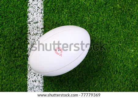Photo of a rugby ball on a grass next to the white line, shot from above. - stock photo