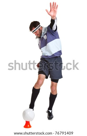 Photo of a rugby player kicking the ball off a tee, cut out on a white background.