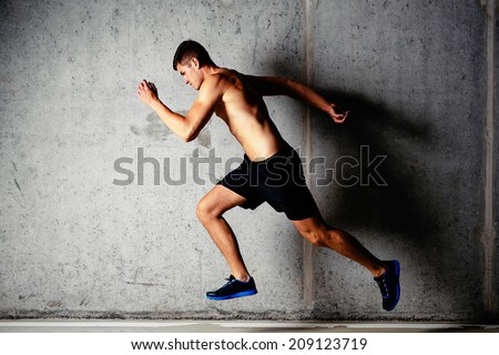 Photo of a running muscular sportsman on a concrete background