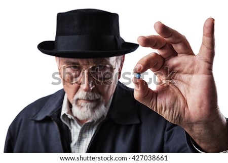 Photo of a senior adult male drug pusher showing off a potent blue pill - stock photo
