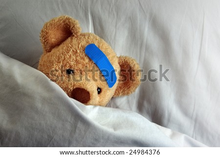 Photo of a sick teddy bear with a blue bandage in bed - stock photo
