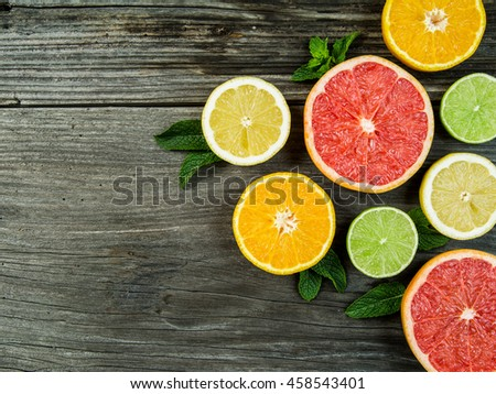 Photo of a sliced grapefruit, orange, lemon, and lime on a old rustic slab of barn board. - stock photo