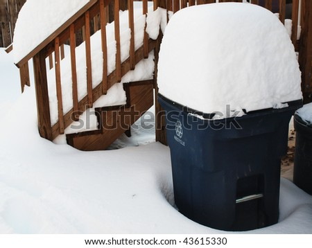 photo of a snow covered recycle bin of a residence after a winter snow blizzard