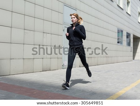 Photo of a sporty woman running in the city - stock photo