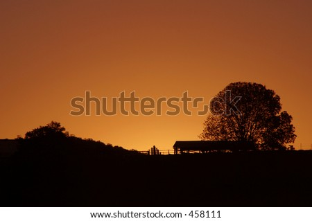 Photo of a sun setting behind a country shed. - stock photo