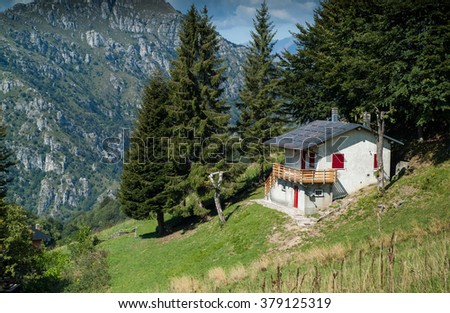 photo of a sunlit traditional house at Piani d'Erna (part of the Alps) near Lake Como in Italy - stock photo