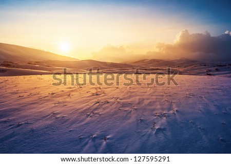 Photo of a sunset at winter snowy mountains, peaceful stunning landscape, amazing seasonal nature, cold weather in the park, beautiful sunny snow field, wintertime scene, icy lands - stock photo