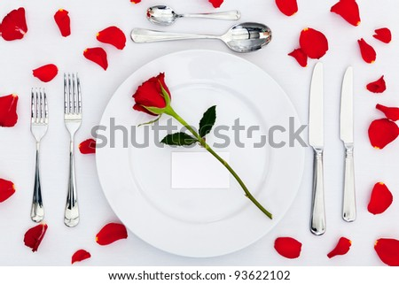 Photo of a table place setting with a red rose and blank card on the plate plus rose petals on the tablecloth. Add your own message to the place card. - stock photo