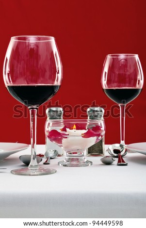 Photo of a table setting with red wine glasses and a floating candle, copy space to add your own message. - stock photo