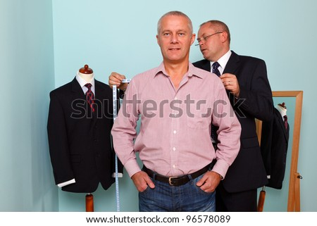 Photo of a tailor measuring the shoulder width of a man for the fitting of a new bespoke suit - stock photo