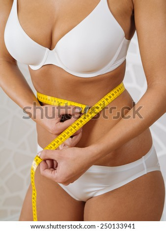 Photo of a tanned slim young woman in underwear measuring her waistline. - stock photo