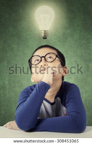 Photo of a thoughtful primary school student thinks idea under a bright light bulb in the class - stock photo