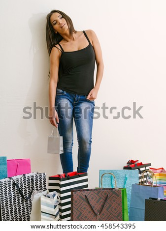 Photo of a tired young woman standing around all her shopping bags. - stock photo